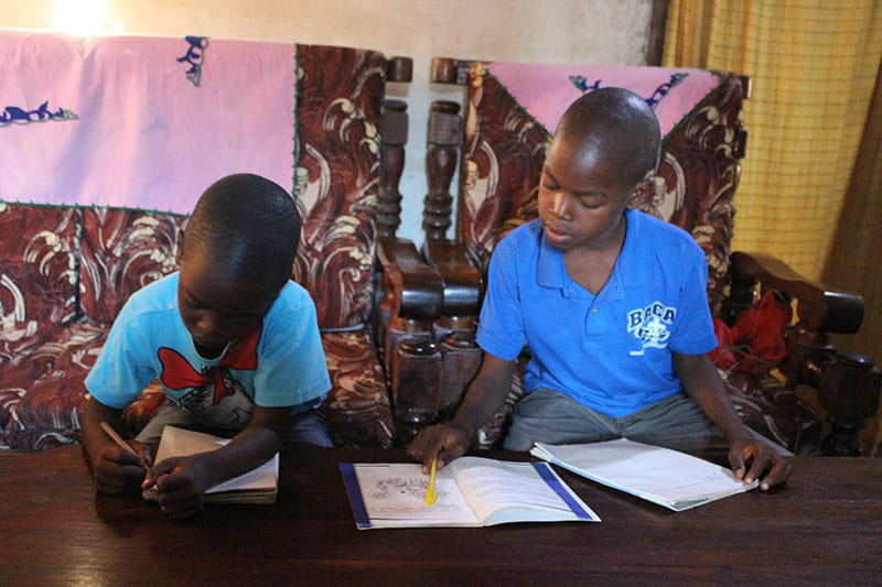 amos and John studying by solar powered light