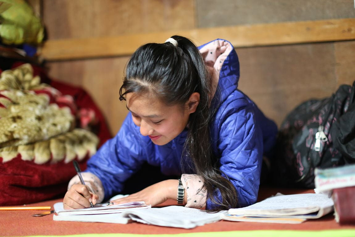 A girl from Nepal studying with electricity provided by hydro-power