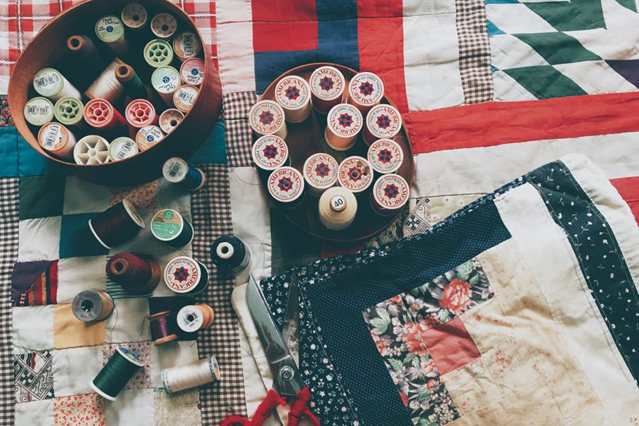 Quilt with reels of cotton.