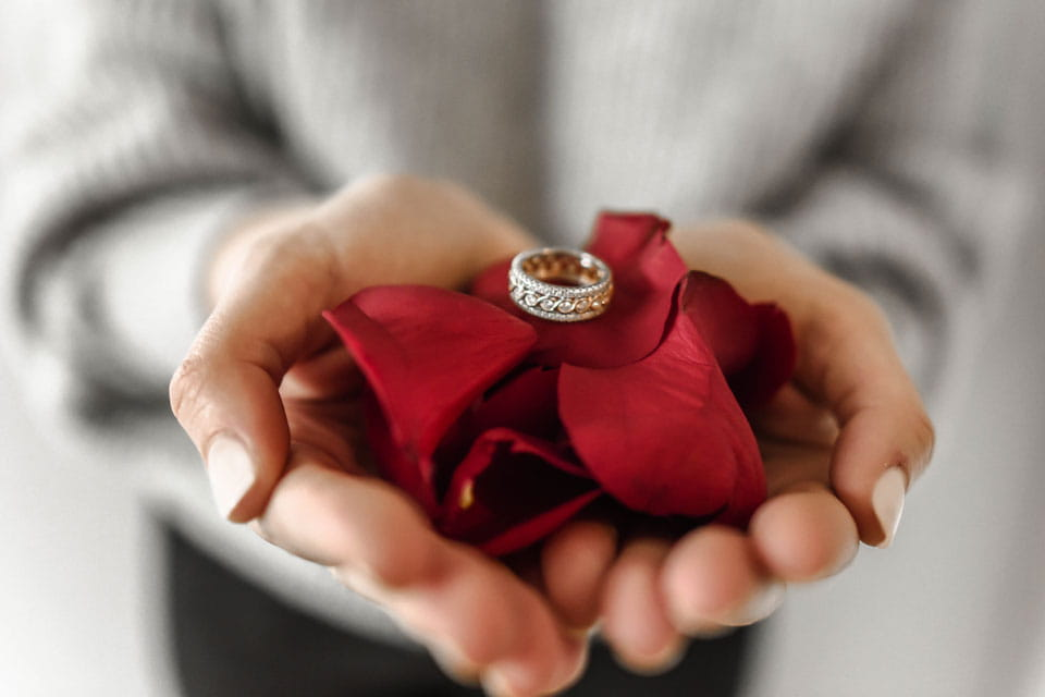 Person holds silver ring on cushion of roses.