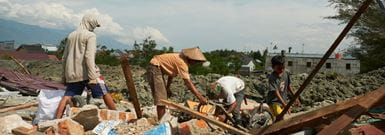 men looking through rubble in Indonesia
