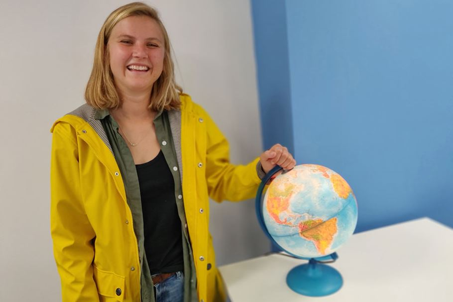 Natalie stands by a globe