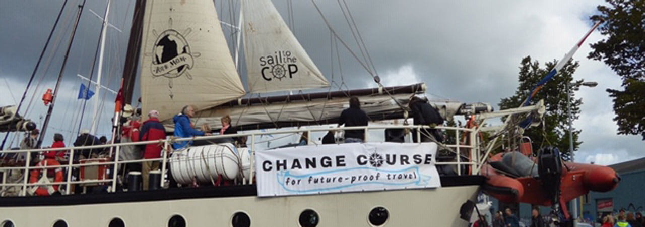 The boat shortly before setting sail with banner proclaiming 'change course'