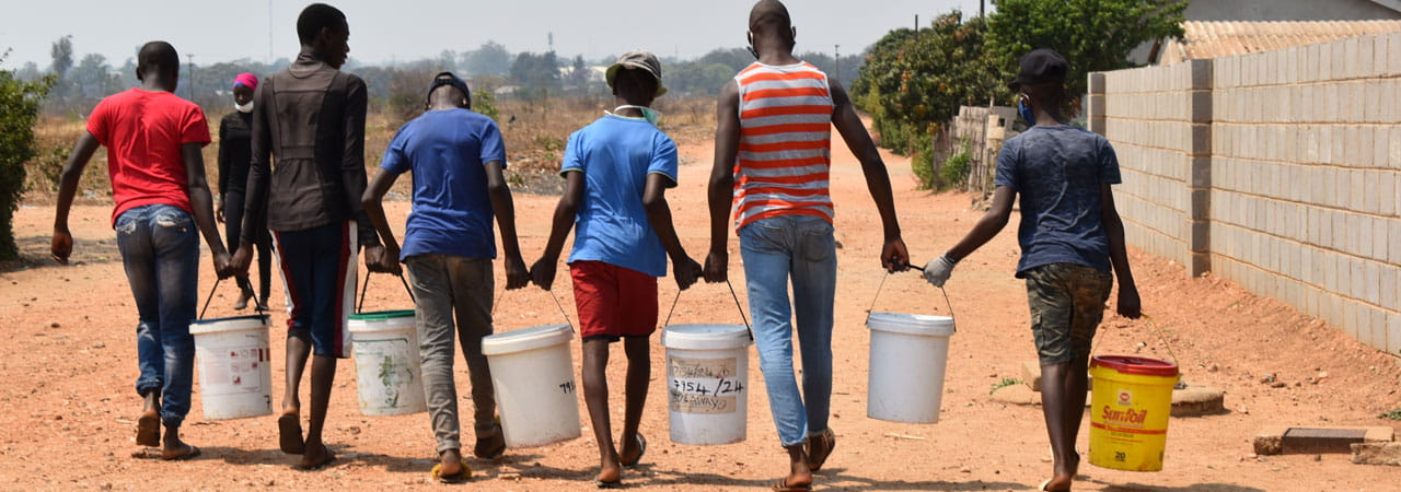 Group of young men carrying water buckets Photo credit: Stewart Muchapera/ Tearfund