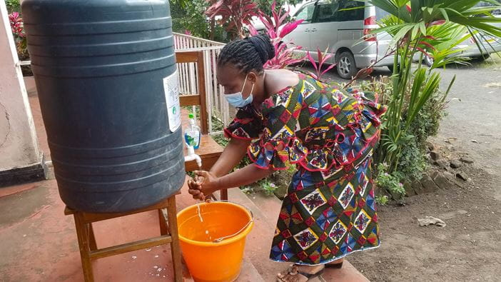 A woman washing her hands at an event where faith leaders attend Covid-19 response training