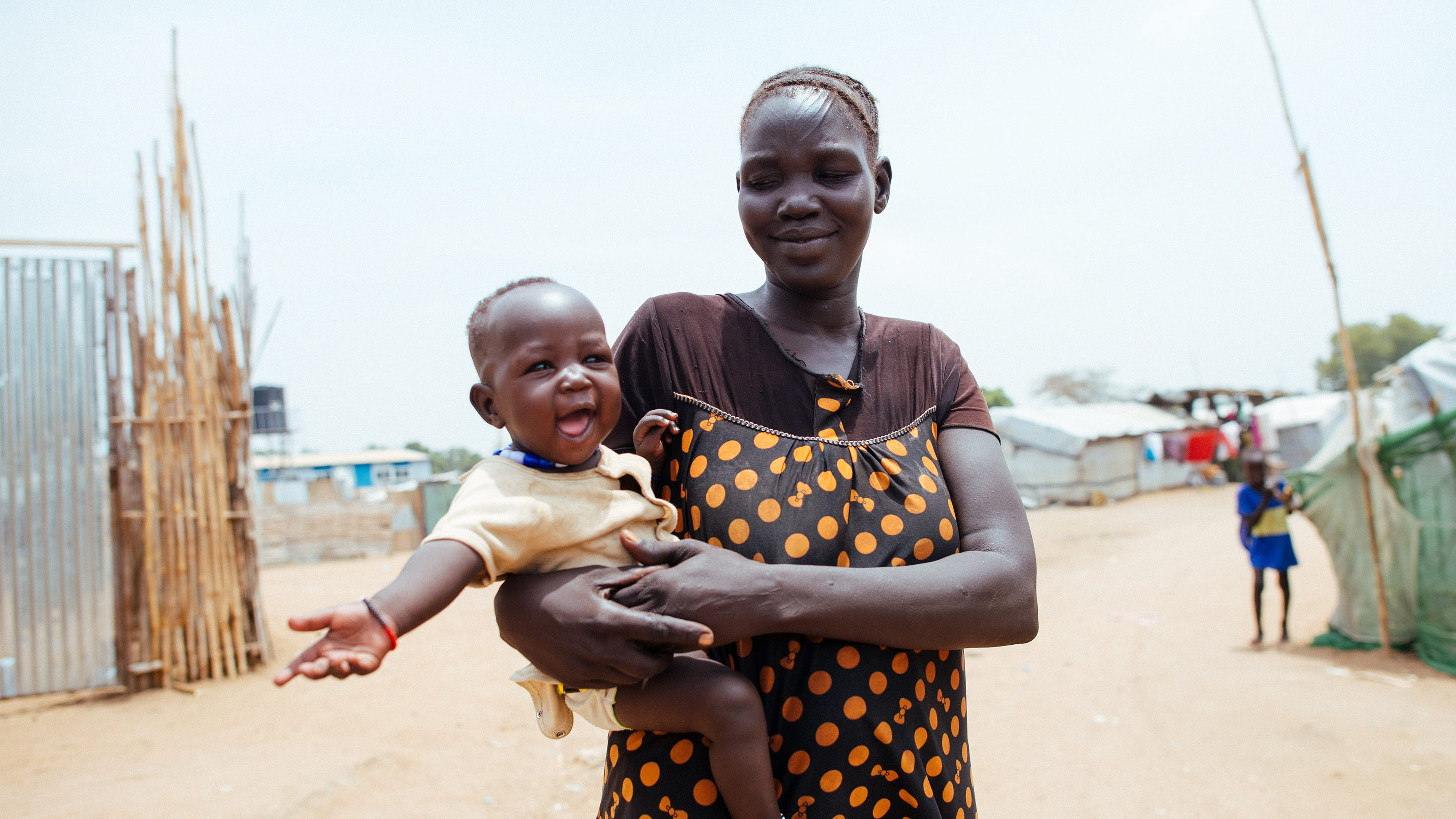 A woman with her 18-month-old daughter, outside their shelter in the Konyo Konyo camp for internally displaced people in South Sudan | Credit: Tom Price/Tearfund