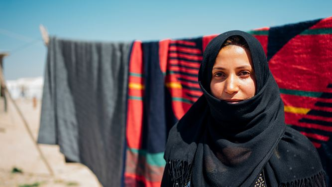 A woman standing in a displacement camp