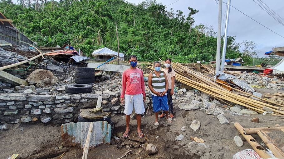 Rowena and her family stand outside their house destroyed by Typhoon Goni