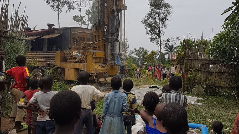 Children gather to watch as drilling the borehole begins | Credit: Tearfund