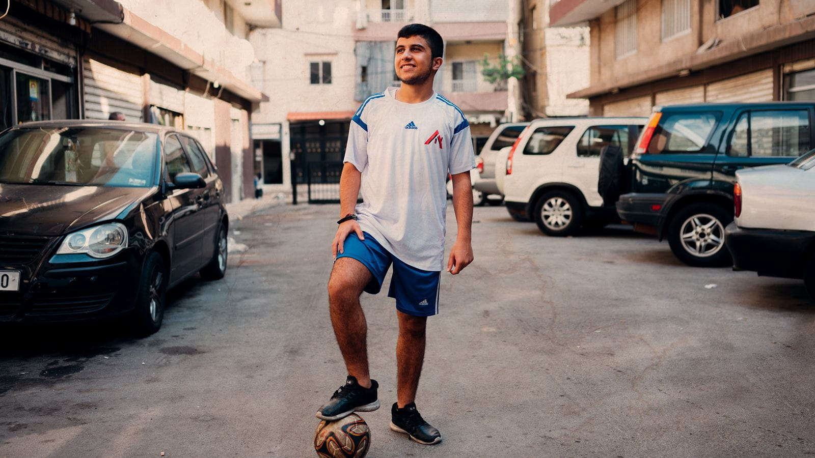 Saif stands with a football in a street in Beirut, Lebanon. Credit: Ruth Towell/Tearfund