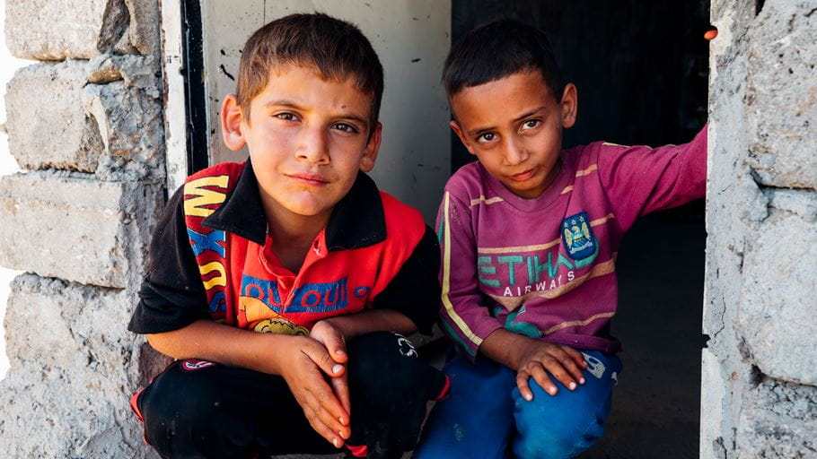 Two boys crouching in a doorway